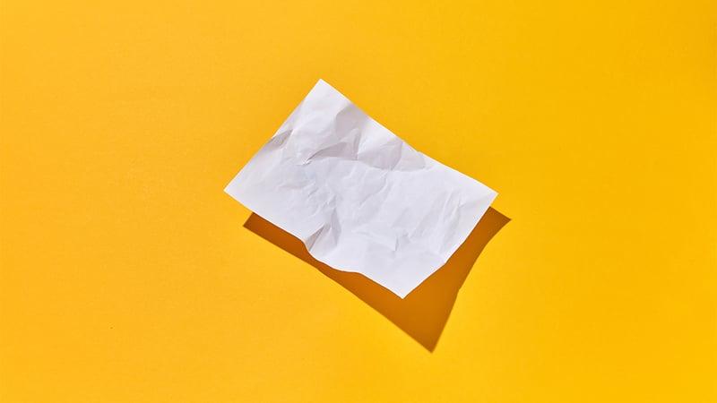 Tyhjä rypistetty paperi keltaisella taustalla